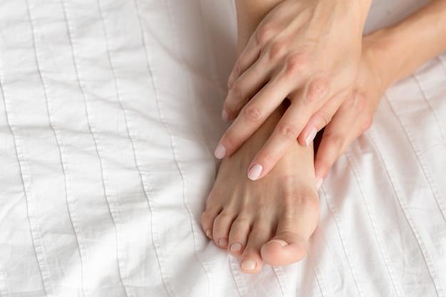 Gambe della donna perfetta e bella sul letto