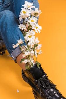 Gambe della donna seduta in stivali con bouquet di fiori all'interno