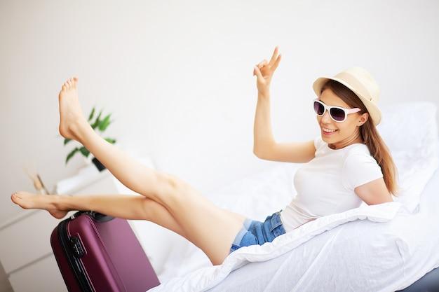Gambe della donna sollevate sul bagaglio, giovane donna a casa sdraiata a letto.