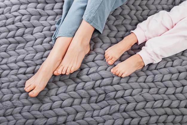 Gambe della figlia e della madre sul plaid lavorato a maglia di lana