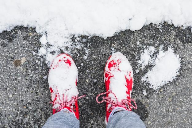 Gambe della persona in stivali su asfalto vicino neve