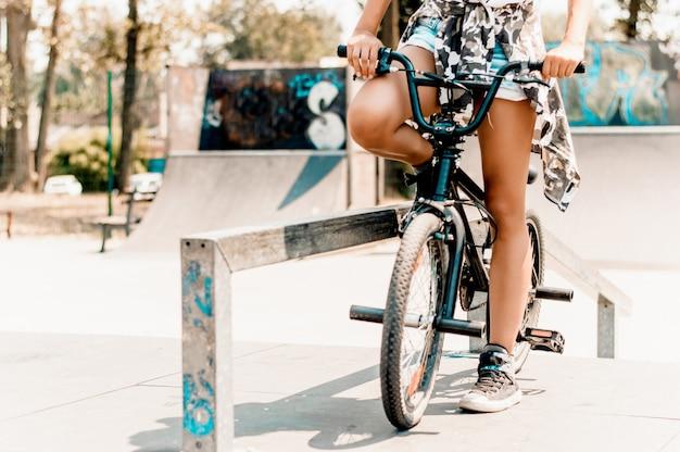 Gambe della ragazza graziosa che si siedono sulla bicicletta nell'ambiente urbano