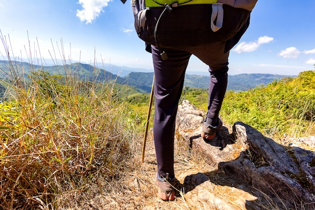 Gambe della viandante che stanno nella cima di una montagna.