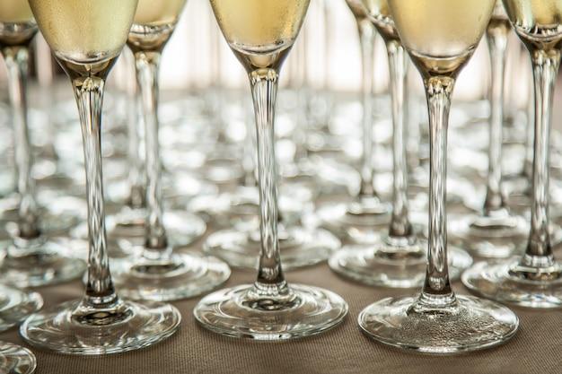 Gambe di bicchieri con champagne freddo, primi piani