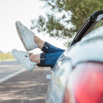 Gambe di donna appesa fuori dalla macchina