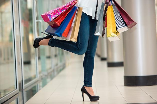 Gambe di donna con borse della spesa