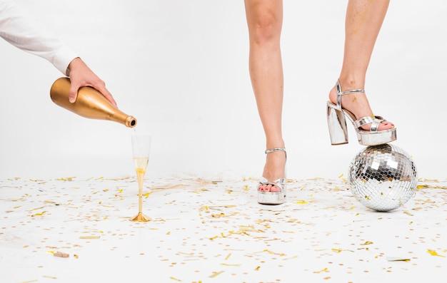 Gambe di donna e bicchiere di champagne sul pavimento