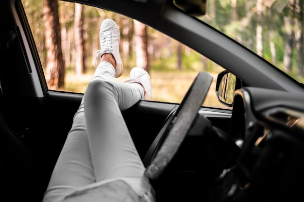 Gambe di donna fuori dal finestrino della macchina