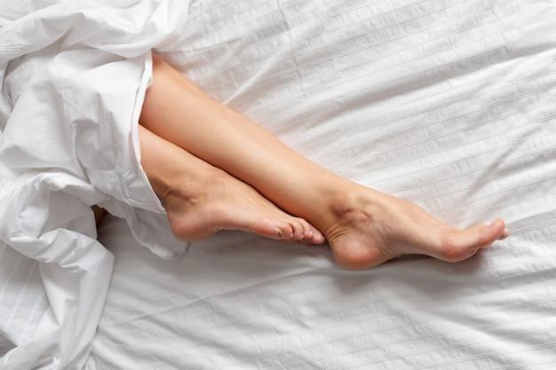 Gambe di donna perfetta e bella sul letto
