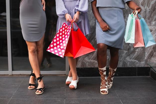 Gambe di donne ad alto angolo con borse della spesa