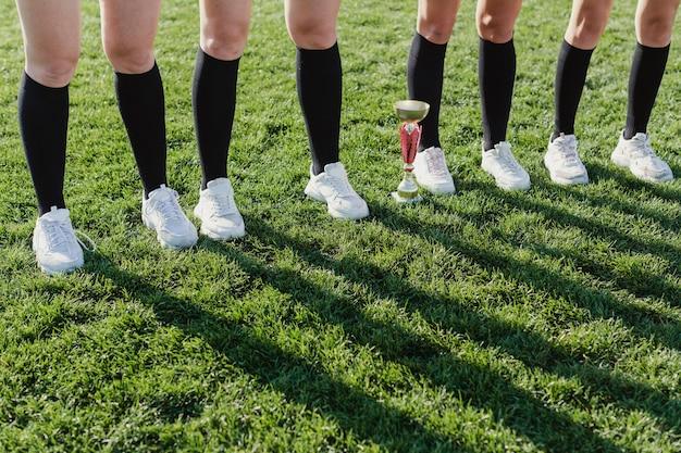 Gambe di donne sedute accanto a un trofeo