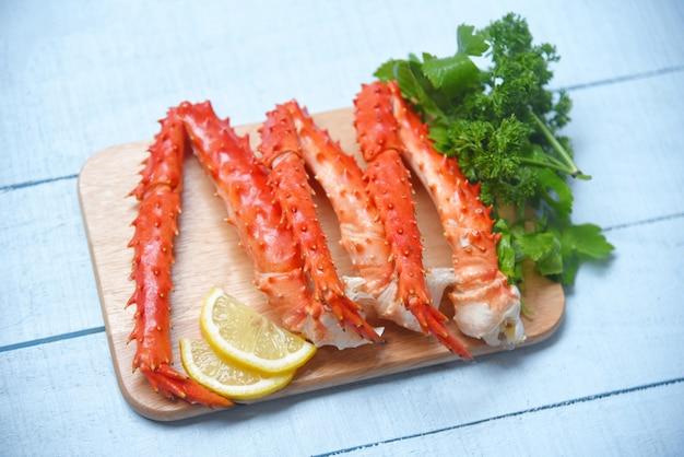 Gambe di granchio del re dell'alaska cucinate sul tagliere di legno con prezzemolo del limone - il pesce rosso dell'hokkaido del granchio ha servito la tavola