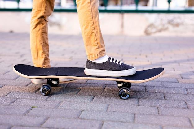 Gambe di skateboarder cavalcando skateboard sulla strada della città