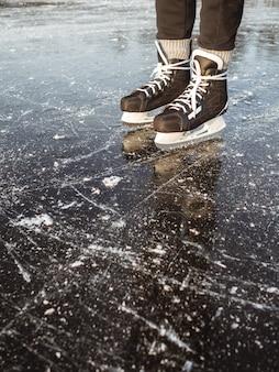 Gambe di un uomo nel pattinaggio su ghiaccio per hockey su ghiaccio