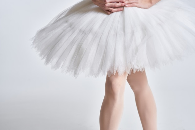 Gambe di una ballerina in scarpe da punta su una parete leggera