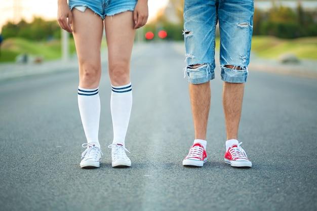 Gambe di una coppia di adolescenti con abiti quotidiani