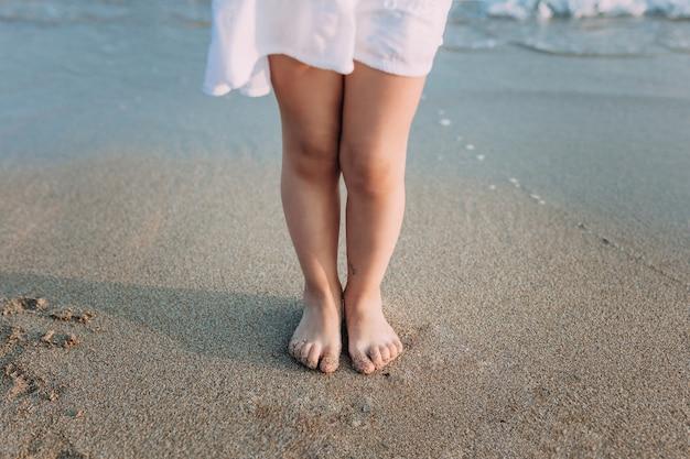 Gambe di una ragazza in abito bianco sulla spiaggia di sabbia di mare
