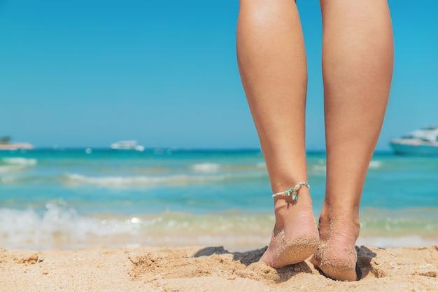 Gambe di una ragazza in riva al mare