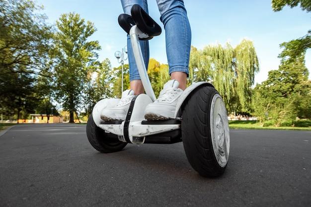 Gambe di una ragazza in scarpe da tennis bianche su un hoverboard bianco in un primo piano del parco
