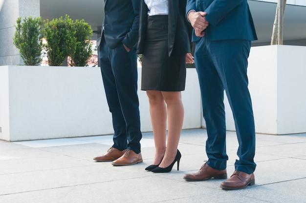 Gambe di uomini d'affari in piedi sul portico accatastato