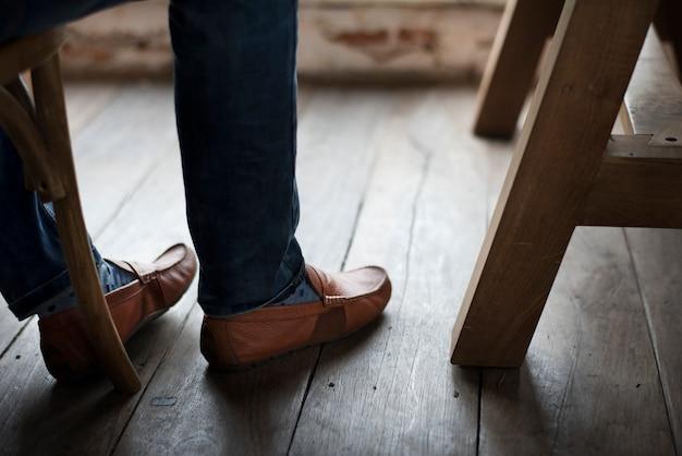 Gambe di uomo adulto piedi dal pavimento in legno