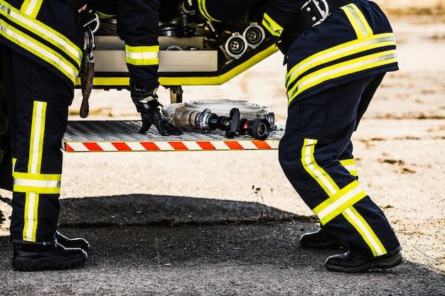 Gambe di vigili del fuoco sul retro del camion dei pompieri