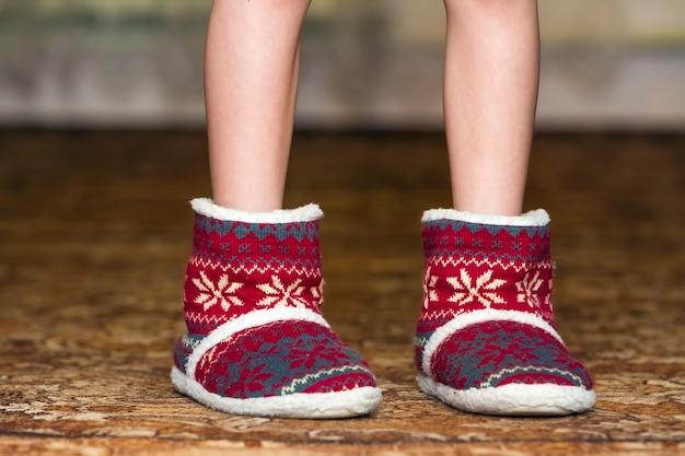 Gambe e piedi nudi del bambino in stivali rossi di natale di inverno con il modello dell'ornamento