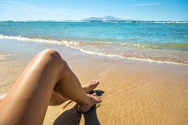 Gambe esili lunghe della giovane donna che si rilassano sdraiati e che prendono il sole sulla spiaggia tropicale della sabbia sotto il sole caldo di estate. cura della pelle, protezione solare e concetto di viaggio in mare.