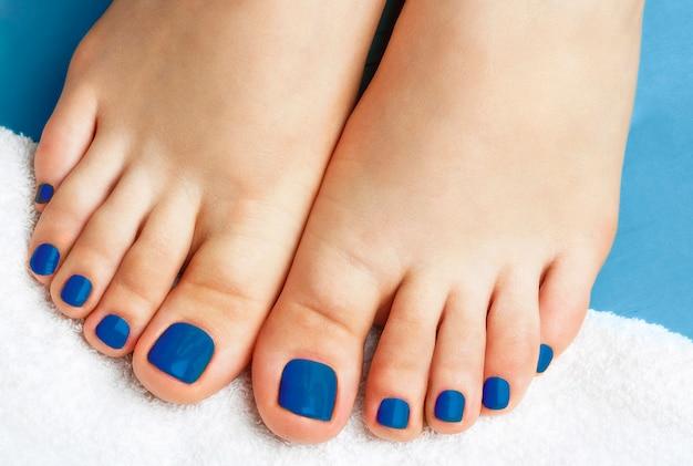 Gambe femminili con il pedicure su una fine bianca dell'asciugamano su, colore di tendenza di concetto dell'anno blu classico 2020.