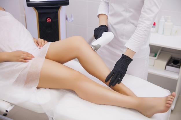 Gambe femminili, donna nella clinica di bellezza professionale durante la depilazione laser