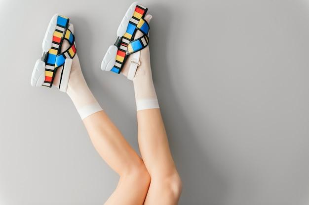 Gambe femminili in calzini bianchi e scarpe alla moda su grigio