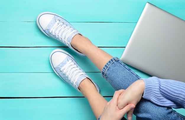 Gambe femminili in jeans e scarpe da ginnastica, computer portatile su un pavimento di legno turchese. tecnologie moderne. generazione z. vista dall'alto. disteso.