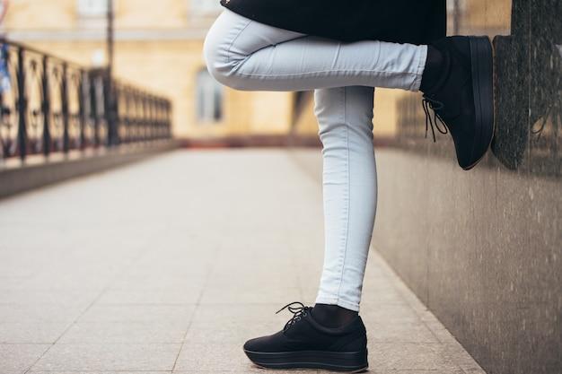Gambe femminili in jeans sul marciapiede mentre si cammina in città