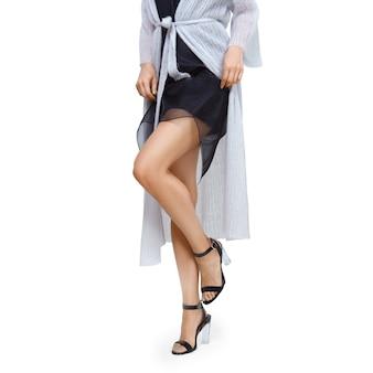 Gambe femminili in scarpe a tacco alto con vestito alzato, abito in maglia.
