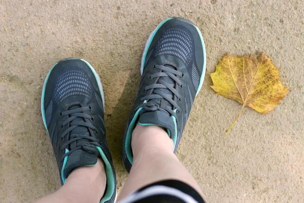 Gambe femminili in scarpe da tennis e foglia gialla, vista ravvicinata dall'alto