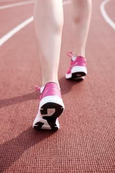 Gambe femminili in scarpe da tennis rosa sullo stadio della pista da corsa