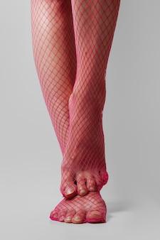 Gambe femminili muscolose lunghe in collant a rete rosa sexy. vista frontale del primo piano.