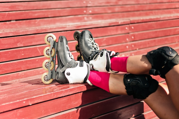 Gambe femminili nei pattini di rullo sui bordi di legno rossi all'aperto