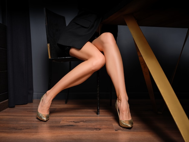 Gambe femminili nude lunghe e sottili in gonna corta