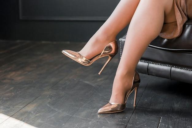 Gambe femminili perfette che indossano tacchi alti dorati che si siedono sul sofà