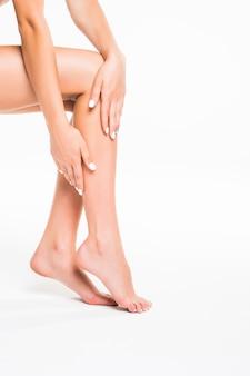 Gambe femminili perfette, isolate sul muro bianco