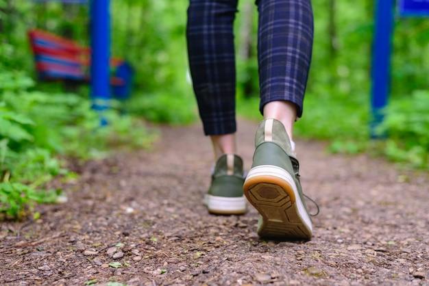 Gambe femminili sottili in leggings scozzesi e scarpe da ginnastica verdi percorrono il sentiero nel bosco. passeggiate all'aria aperta