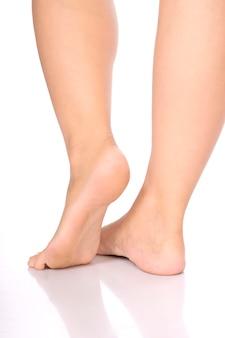 Gambe graziose lunghe della donna che intraprendono punto isolato su bianco