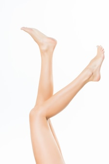 Gambe graziose lunghe della donna isolate sulla parete bianca