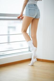 Gambe lunghe della donna con bella pelle liscia. primo piano della mano femminile che tocca la pelle morbida e setosa perfetta glabra. depilazione ed epilazione, concetti di cura del corpo di bellezza