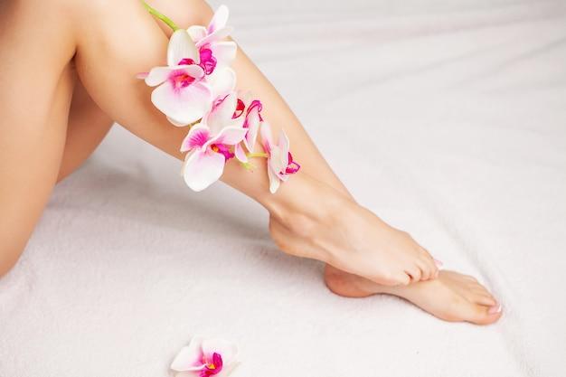 Gambe lunghe di una donna con una manicure fresca e fiori di orchidea