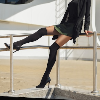 Gambe lunghe e sottili femminili in calzettoni sopra collant e gonna corta in pelle che si siede sulla ringhiera.