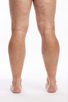 Gambe maschi pelose nude su una parete bianca. avvicinamento.
