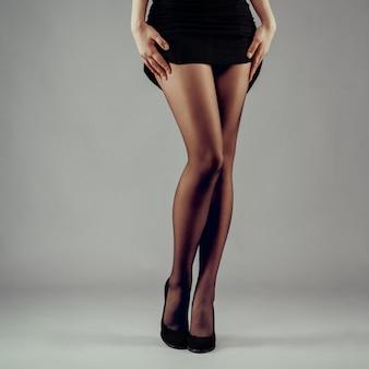 Gambe sexy lunghe femminili in scarpe tacco alto e vestito di sollevamento.