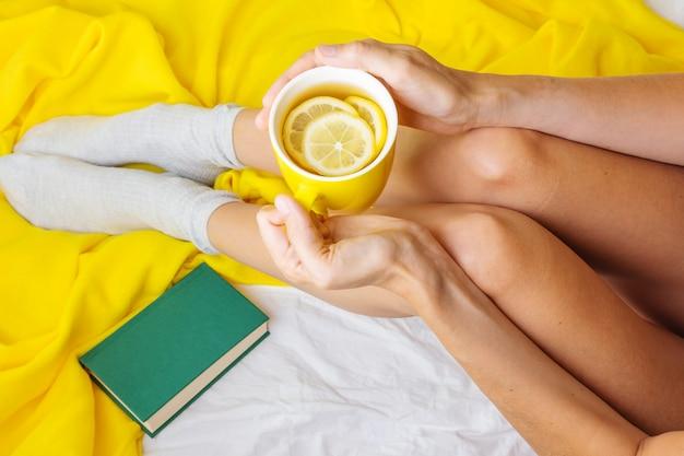 Gambe snelle femminili su un plaid giallo e un lenzuolo bianco. nelle mani di una tazza gialla con tè e limone.